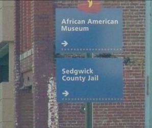 Két útmutató tábla egy oszlopban. Felső: 'African American Museum →' Alsó: 'Sedgwick County Jail →'